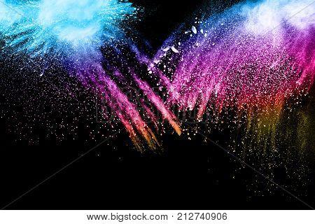 Explosion of colored powder on black background. Freeze motion of colorful splashed powder. Painted holi splattered.