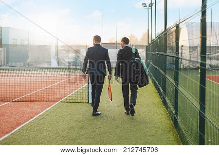 Business, partnership and sport. Business partners practicing sport together. Successful business men walking looking to tennis court before a tennis set, wearing suits and tennis equipment.