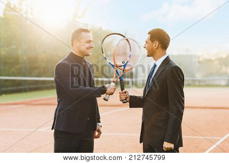 Two businessmen in suits holding tennis rackets crossed looking to each other, announcing their intention to win, smiling being ready to compete. Business, sport, competition, partners.
