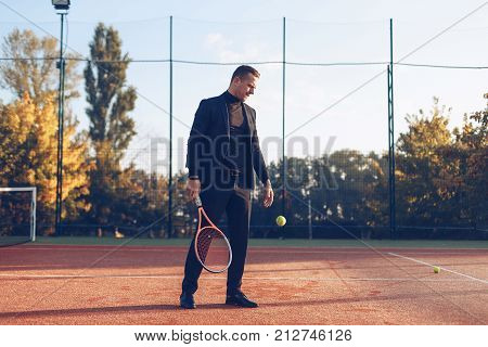 Portrait of confident businessman holding tennis racket in hand looking to jumping ball against tennis court background. A portrait of a tennis player wearing suit with a racket.