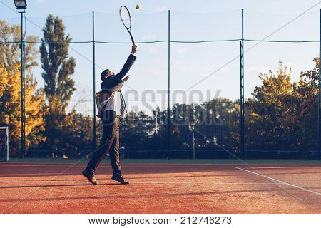Businessman holding tennis racket throwing ball ready to serve against tennis court background. A portrait of a tennis player wearing suit with a racket.