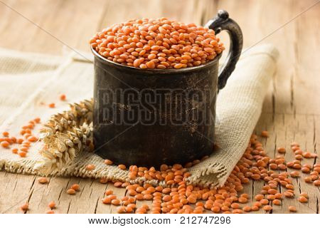 Bowl of legumes red lentilson wooden background