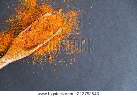 Dried saffron spice on black background. Raw Organic pistil powder saffron are scattered on the table. Red Saffron Spice in a wooden spoon on black background