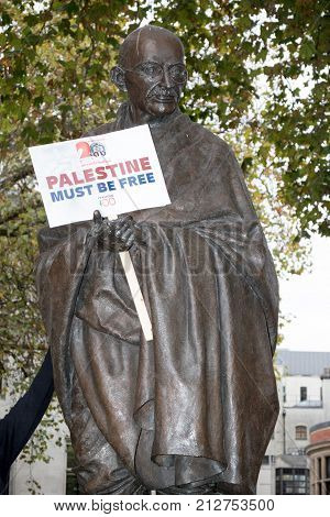 4th November 2017 London United Kingdom:-Statue of Mahatma Gandhi in Parliment square holding a pro Palestine placard placed by protesters