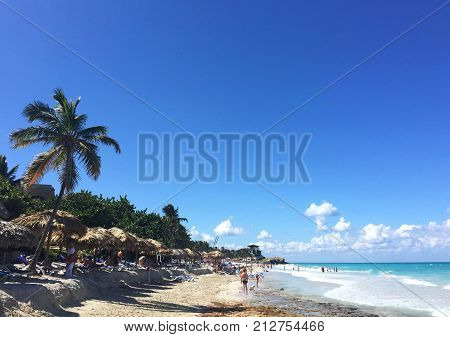 Beautiful view of the ocean. Waves, palm trees and white sand. Atlantic coast of Cuba. People on the beach Varadero