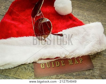 Holiday Travel Guide Background. Holiday travel concept with Santa hat, aviator sunglasses and a map for surviving the busy holiday travel season.