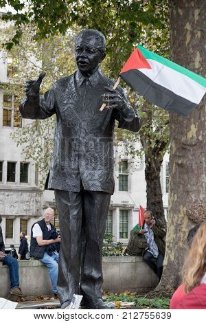 4th November 2017 London United Kingdom:-Statue of Nelson Mandela holding a Palestine flag placed by a protester in Parliment Square