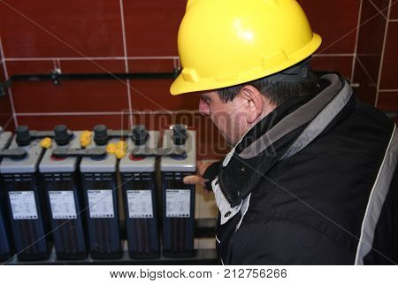 Electrician with yellow helmet check battery pack