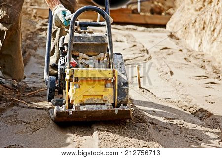 Worker use vibratory plate compactor to compacting ground at road repair