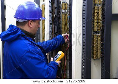 Worker in blue helmet make electrical measurements