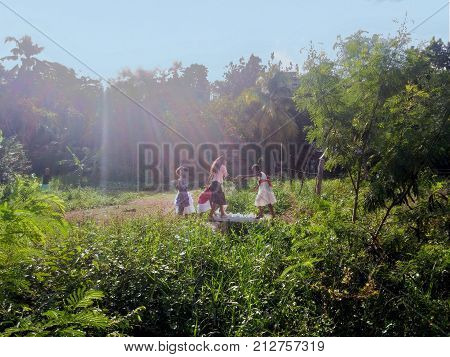 SANTO DOMINGO, DOMINICAN REPUBLIC - OCT 25, 2015: Poor girls crossing an improvised bridge with the door of a refrigerator over a ditch in Santo Domingo, Dominican Republic
