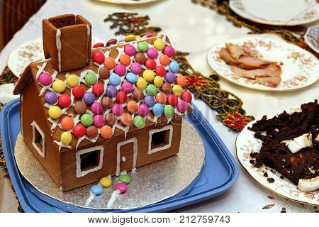 Traditional Festive Gingerbread House On A Table With The Remains Of Christmas Dinner And Pudding