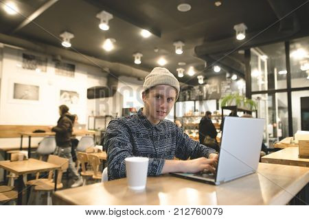A hipster student sits in a cozy cafe with a laptop and works. A young man enjoys intranet on a laptop and drinks coffee. A look at the camera.