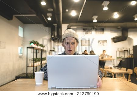 A young man is working in a cafe and looks surprised at the laptop screen. The student enjoys an intranet in a cozy cafe