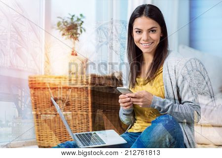 Convenient gadgets. Beautiful cheerful young woman sitting with a modern convenient smartphone while her being on her knees