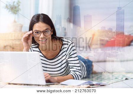 Enthusiastic person. Cheerful qualified specialist having a productive working day at home while sitting in front of a laptop