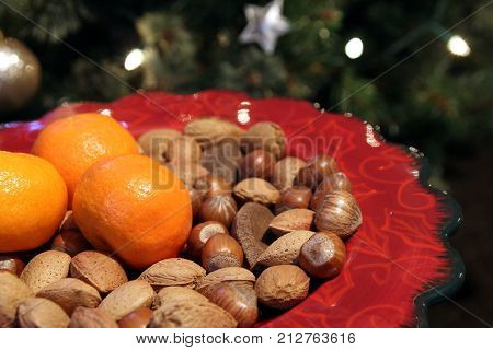 Pretty Red Christmas Plate With Traditional Festive Almonds, Hazelnuts And Brazil Nuts, And Three Sa