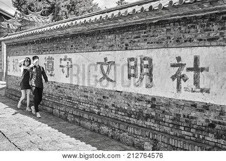 Lijiang, Yunnan, China - September 28, 2017: Young Chinese Walk In The Shade Of Dayan Wall. Old Town