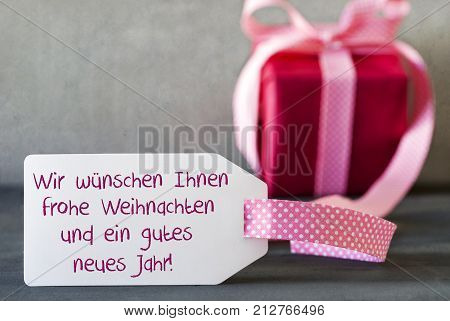 Label With German Text Wir Wuenschen Frohe Weihnachten Und Ein Gutes Neues Jahr Means We Wish You A Merry Christmas And A Happy New Year. Pink Gift Or Present With Gray Cement Background