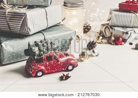 Modern Christmas Ornaments And Car Toy With Tree, Presents Cones Anise On White Wooden Background. M