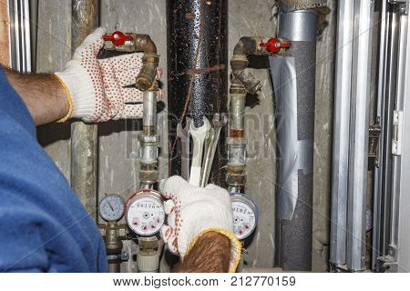 plumber repairs pipes in plumbing unit. Hands plumbing with spanners on background of pipes manometers and filters