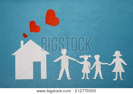 Family and home love concept. Paper house and family on blue textured background. Dad mom daughter and son hold hands. Red hearts from pipe at home. Happy family