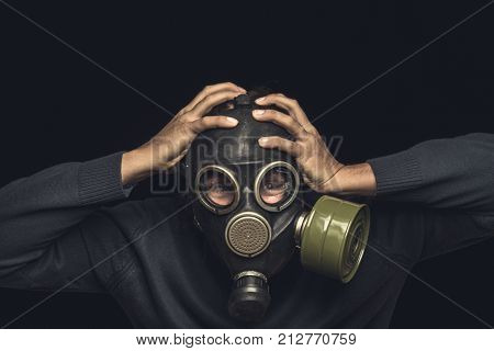 Man in gas mask holds his hands behind his head, emotion of panic and catastrophe or disaster concept, dark toned
