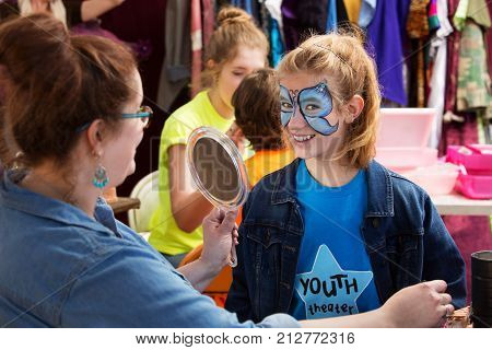 Female adult showing teen actress her makeup on mirror backstage