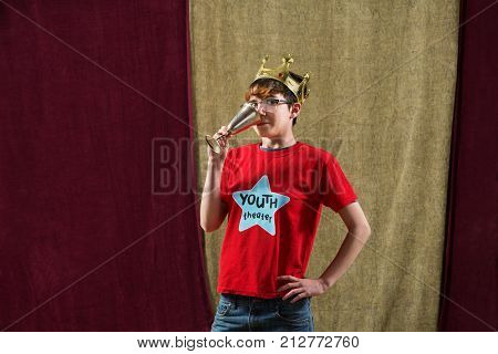 One young actor dressed as king wearing crown drinks from silver goblet