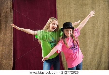 Two playful friends pose for at acting camp pose with arms spread wide