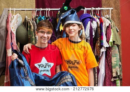 Smiling young friends pose together in dressing room as one holds his costume