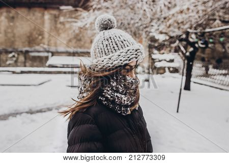 Stylish Hipster Woman In Knitted Hat Standing In Snowy City Street. Beautiful Fashionable Girl In Wa