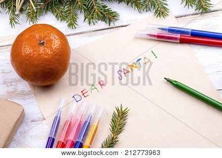 on the wooden table are an old yellow paper that says, Dear Santa Claus red, pencils, pens assorted colors gift and tree branches for the new year