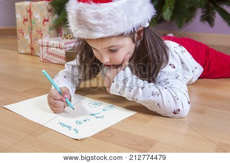 Little girl preparing The Santa Letter. She painting a sheet with header in English