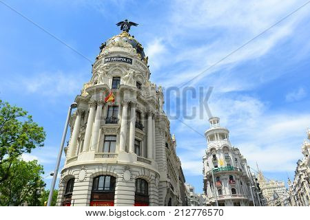 MADRID - JUN. 6, 2013: Metropolis Building (Edificio Metropolis) and Grassy Building (Edificio Grassy) in Madrid, Spain. Metropolis Building is one of the most famous Beaux-Arts style landmark.