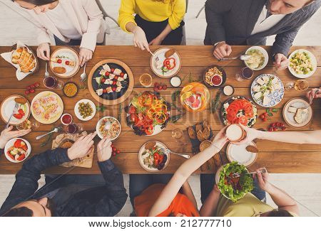 People eat healthy meals at festive table served for party. Friends celebrate with organic food on wooden table top view. Happy company having lunch, taking salad dish.