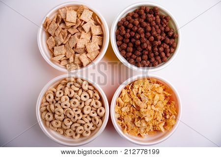 Various corn flakes in different plates, four plates with flakes, pads, chocolate balls, circles, and flakes, isolated on white background, top view