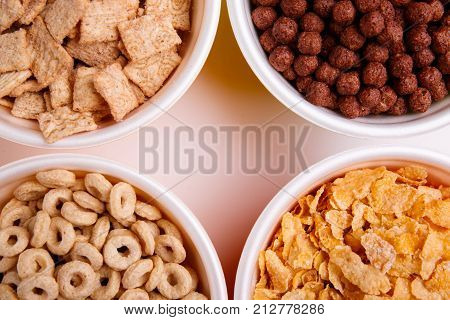 Various corn flakes in different plates, four plates with flakes, pads, chocolate balls, circles, and flakes, isolated on white background,