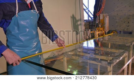 Cleaning and washing. Professional window washing equipment. Early spring windows cleaning. Maid cleans window. Male janitor using a sponge to clean a window in an office wearing an apron and gloves as he works