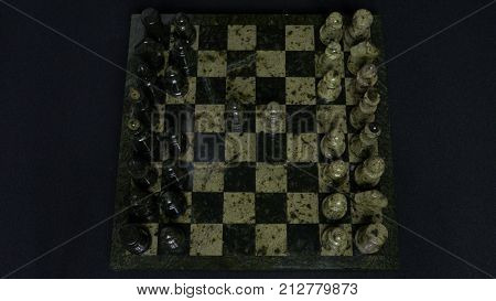 Checkmate. Start Of A Chess Game, the Figures Are Lined Up And A Person Makes The First Move. Hand moving a knight chess piece on chessboard. Man's hands play chess, checkmate in chess