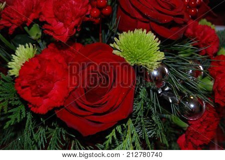 Red and green winter holiday flower arrangement, with silver ornaments.