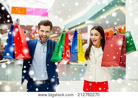 Photo Of Cheerful Stylish Successful Crazy Happy Young Lovely Couple Raised In Hands Colored Shoppin