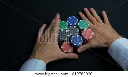 Stack of poker chips and two hands on table. Closeup of poker chips in stacks on green felt card table surface. Poker chips and hands above it on green table.