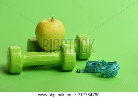 Dumbbells In Green Color, Twisted Measure Tape And Fruit