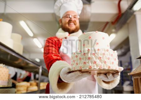 Santa Claus a pastry cooks a cake in the kitchen on Christmas Day.