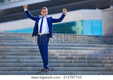 Portrait Of Cheerful Young Businessman In Blue Suit Standing On Office Building Background. Career,