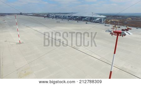 Aerial view of the modern international airport terminal. Traveling around the world. Empty airport aerial. View of runway at the airport. Airfield marking on taxiway is heading to runway