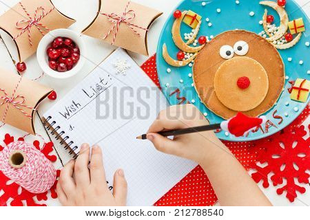 Child hand writes a wishlist for santa claus Christmas concept