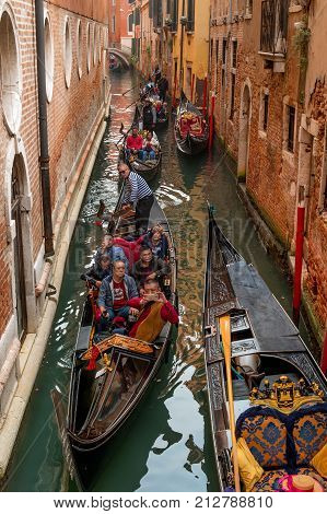 Venice Italy - October 13 2017: Gondoliers take tourists through the narrow canals of Venice. Tourists of their China. The tourist is photographed on the phone.