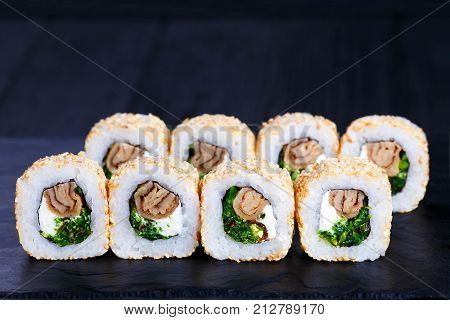 Delicious Sushi Rolls With Chuka Seaweed, Omelet And Cream Cheese Inside, Served On Black Stone Slat